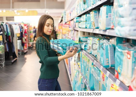 Pregnant woman buys diapers at the supermarket, portrait of young happy mother in shop mall #1021867009