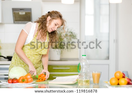 pregnant woman consulting a recipe while cooking in her kitchen