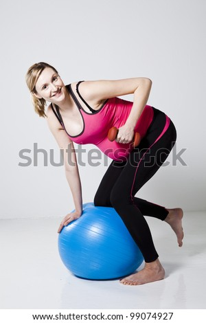 Pregnant woman doing a rowing exercise with dumbbells while kneeling on a fitness ball