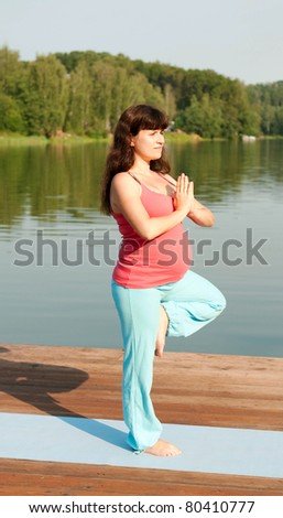 pregnant woman doing yoga on nature