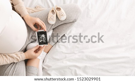 Pregnant woman enjoying future motherhood with first ultrasound photo of her baby, top view with free space Stock photo ©