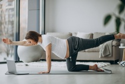 Pregnant woman exercing yoga at home