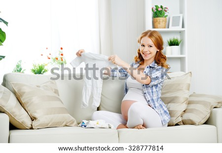 0dedc4ca322 pregnant woman expectant mother prepares clothing items for the newborn  baby  328777814