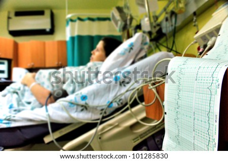 Pregnant woman feels hard contraction in a hospital labor delivery room.  Concept photo of pregnancy, pregnant woman, newborn and baby.