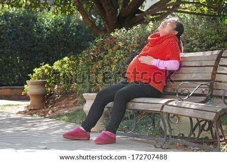 Pregnant Woman Happy and Laughing on a Park Bench