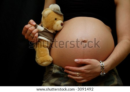 Pregnant woman holding a teddy bear and her belly.