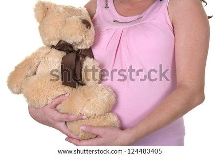 Pregnant woman holding a teddy bear wearing pink in the studio