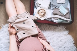Pregnant woman holding baby bodysuit and packing maternity hospital bag. Beautiful mother during pregnancy waiting for baby preparing suitcase of clothes, toy and necessities for newborn child birth.