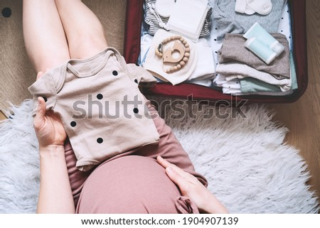 Pregnant woman holding baby bodysuit and packing maternity hospital bag. Beautiful mother during pregnancy waiting for baby preparing suitcase of clothes, toy and necessities for newborn child birth. Photo stock ©