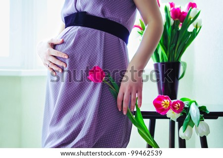 pregnant woman holding her tummy and tulip