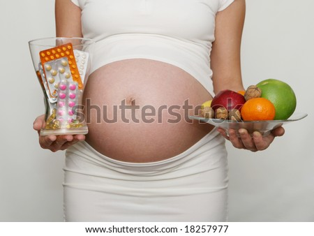 Pregnant woman holding medicine and fruits. Nine month. Third trimester