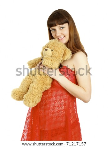 Pregnant woman holding teddy bear on her belly, isolated on white background.