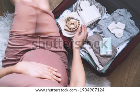 Pregnant woman hugging belly and packing maternity hospital bag. Beautiful mother during pregnancy waiting for baby preparing suitcase of clothes, toy and necessities for newborn child birth.