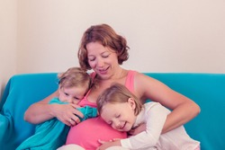 Pregnant woman hugging his little daughters. Selective focus.