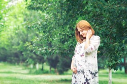 Pregnant woman in a beautiful summer tunic on a walk in the garden on the background of greenery
