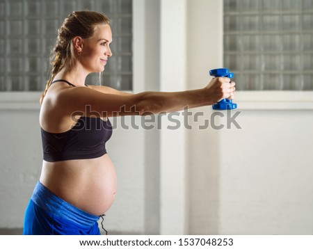 Pregnant woman in her thirties exercising in a gym doing shoulder exercises with dumbbells.
