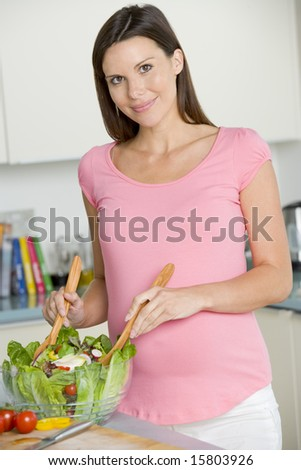 Pregnant woman in kitchen making a salad and smiling