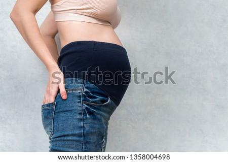 Pregnant woman in maternity pants. Pants with a rubber band on the abdomen. Belly closeup. Gray background. Free space #1358004698