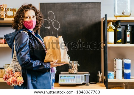 Pregnant woman in protective mask with mesh bag weighs glass jar with nuts. Woman chooses products in zero waste shop. Sustainable shopping at local business. Safety in public place. Covid-19 epidemic Photo stock ©