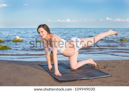 Pregnant woman  in sports bra doing exercise in relaxation on yoga pose on sea