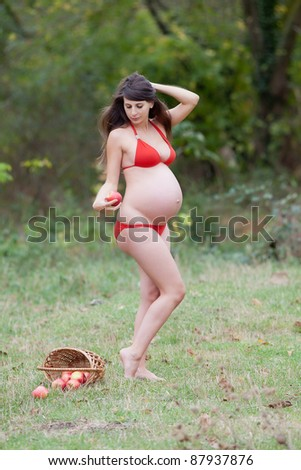 Pregnant woman in the autumn park. Expectant mother in red swimwear posing on open air