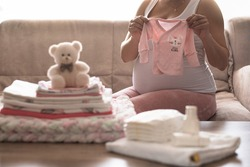 Pregnant woman is getting ready for the maternity hospital, packing baby stuff. pregnant woman preparing and planning baby clothes. Pregnant woman holding bodysuit new born baby. Preparing stuff for