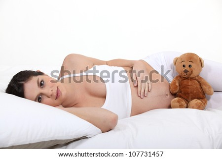 Pregnant woman laying on bed with teddy
