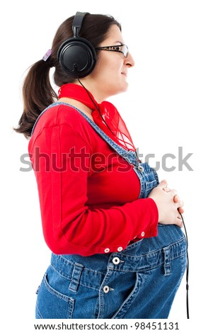 Pregnant woman listening music at headphones, isolated on white