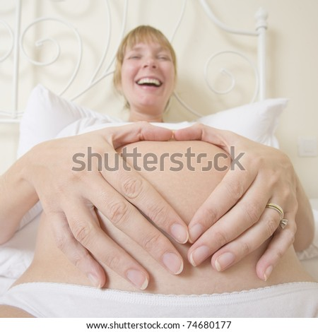 Pregnant woman making a heart shape with her hands on her belly.