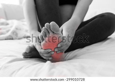 Pregnant woman massaging her painful foot, red hi-lighted on pain area