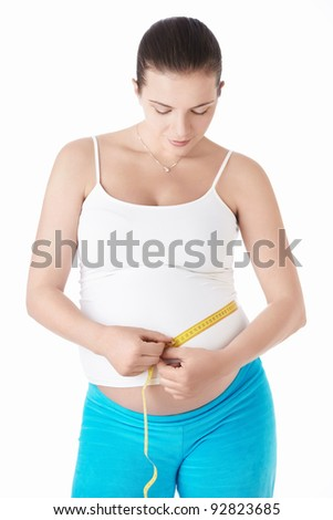 Pregnant woman measuring belly centimeter on a white background