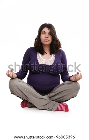 Pregnant woman meditating - stock photo