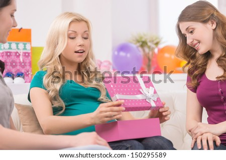 Pregnant woman on baby shower. Beautiful pregnant woman receiving gifts from her friends