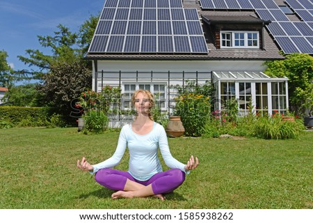 Pregnant woman performing yoga in garden of solar paneled house