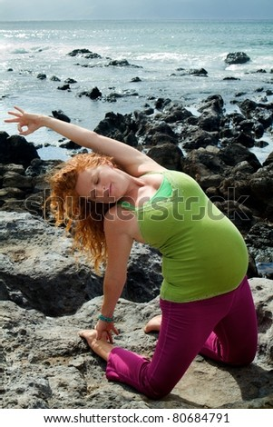 Pregnant woman performs yoga pose on a beach in Maui, Hawaii.