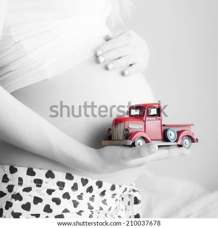 Pregnant Woman plays with a tinny little toy car