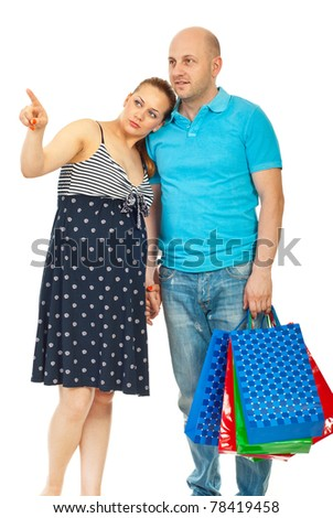 Pregnant woman pointing and showing something to her husband at shopping isolated on white background