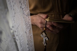 Pregnant woman praying by the window. Praying hands holding cross and book