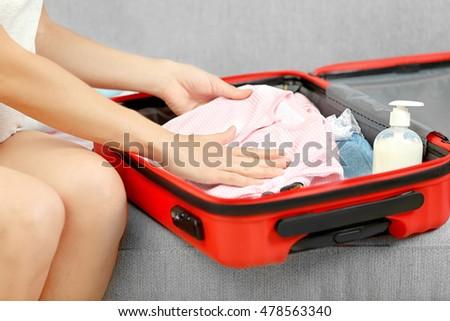 Pregnant woman preparing baby clothes #478563340