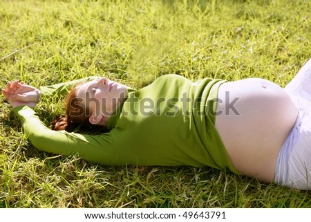 pregnant woman redhead laying on grass garden park relaxed