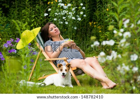 Pregnant woman relaxing in the garden stock photo for Gardening while pregnant