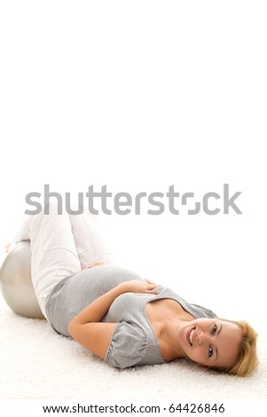 Pregnant woman relaxing on the floor after exercising with a large ball - isolated, copy space