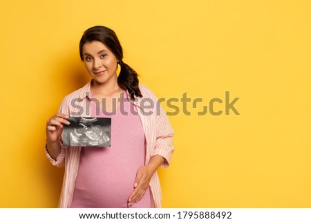 pregnant woman showing ultrasound scan while touching belly on yellow Stock photo ©