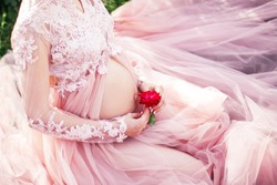 pregnant woman sits in a pink dress with lace and holds a flower in her hands