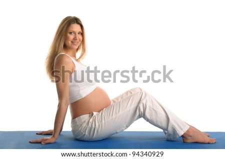 Pregnant woman sitting and practicing yoga isolated on white