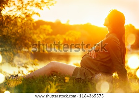 Pregnant Woman sitting on green grass, looking on river on sunset, touching her Belly and dreaming. Enjoying Healthy Pregnancy. Pregnant tummy. Beauty Expectant girl outdoor in summer park in sun glow