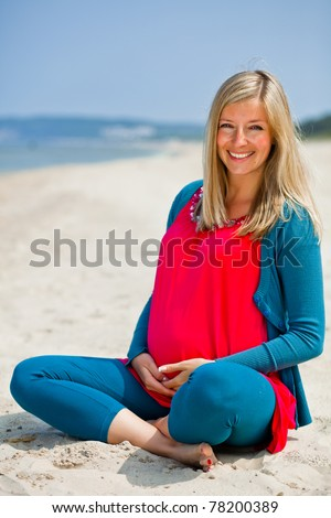 Pregnant woman sitting on the beach