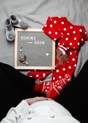 Pregnant woman sitting with a coming soon Baby announcement sign. Coming soon Christmas concept. Pregnancy belly. Blank space.