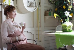 Pregnant woman sitting with cup