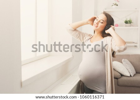 Pregnant woman standing at window and listening music in headphones. Young expectant lady enjoying favorite song home, copy space. Relax, leisure, pregnancy concept #1060116371